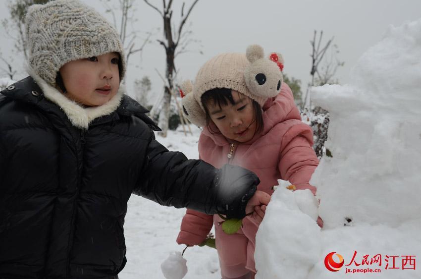 南昌摩天轮旁,两个小孩子正堆雪人