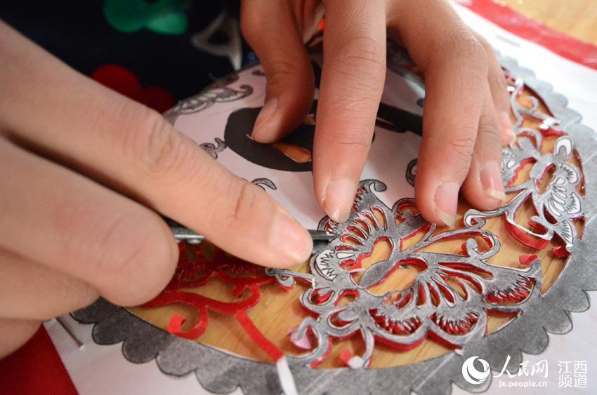 """南昌桃花小学的小学生们正在剪纸""""庆祝元旦""""."""