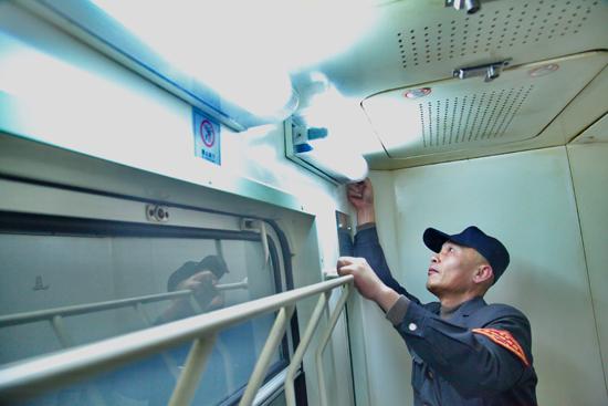 设备所长在维修列车厕所照明灯,确保服务设备作用良好.-南昌铁路